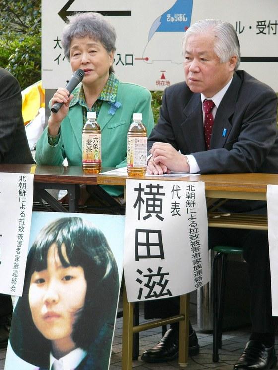 1997년 일본 니가타현 해안에서 북한에 납치된 요코타 메구미(당시 13세)의 아버지 시게루 씨와 어머니 사키에 씨가 2005년 딸의 사진을 걸어 놓고 집회에 참석했을 당시의 모습. [지지통신]