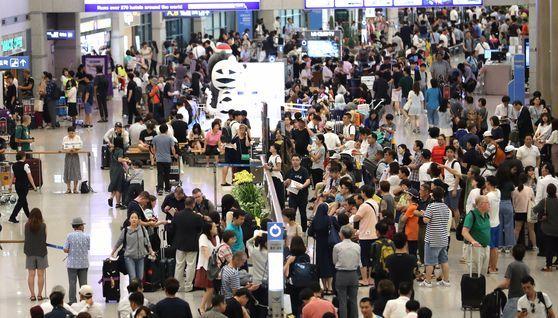 휴가철에 붐비는 인천공항 입국장 . [연합뉴스]