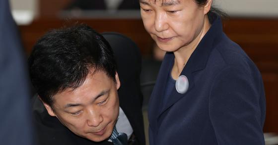 뇌물혐의 등으로 구속 기소된 박근혜 전 대통령(오른쪽)이 지난 5월 23일 오전 서울 서초동 서울중앙지방법원에서 열린 첫 정식 재판에 출석해 유영하 변호사의 안내를 받고 있다. 임현동 기자