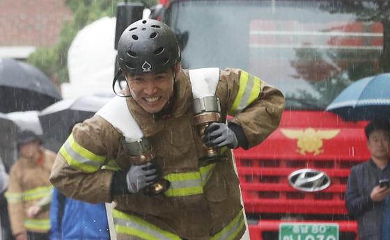 지난 11일 충남 천안시 중앙소방학교에서 열린 전국 소방기술경연대회에서 한 소방관이 소방호스를 메고 목표지점을 향해 달리고 있다. [연합뉴스]
