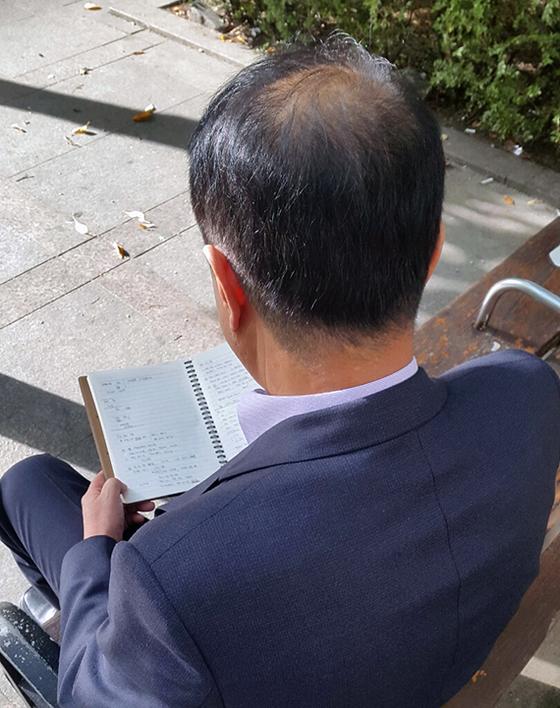지난달 숨진 서울시청 공무원의 아버지 김모씨가 아들의 업무수첩을 읽고 있다. [임선영 기자]