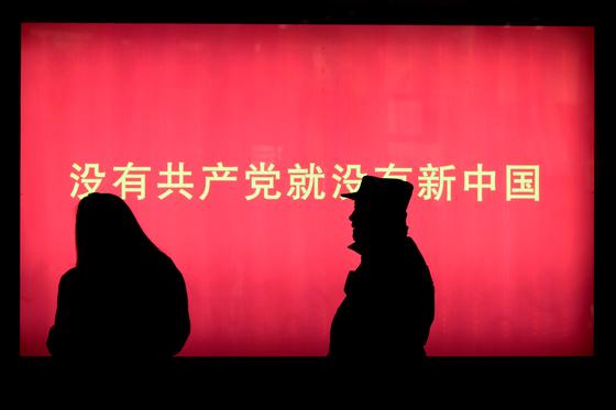 """중국 공산당 당대회를 사흘 앞둔 15일 베이징 시내를 행인들이 걷고 있다. 벽에 쓰인 문구는 '공산당 없이는 새로운 중국도 없다""""는 의미다. [AP=연합뉴스]"""