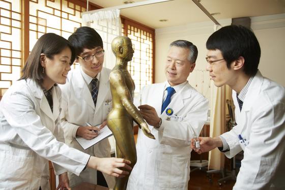 한의사들이 인체 모형을 통해 기와 혈자리에 대해 연구하고 있다. [중앙포토]