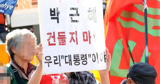 21일 한 집회 참가자가 '박근혜 건들지마. 우리 대통령이야'이라는 푯말을 들고 시위에 참가하고 있다. [뉴시스]