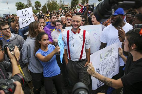 19일(현지시간) 미국 플로리다대학에서 리처드 스펜서의 연설장 밖 거리에서 한 백인우월주의자를 향해 인종차별 반대 시위자들이 항의하고 있다. [AP=연합뉴스]