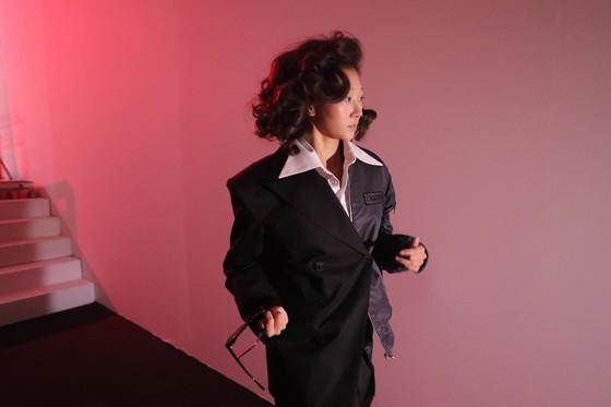 한 여성 모델이 어두운 백스테이지로 돌아오자 선글라스를 벗고 있다. 신인섭 기자