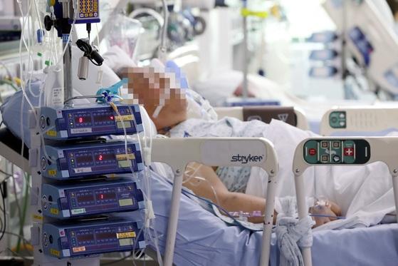 한 환자가 산소호흡기를 부착한 채 중환자실에 누워 있다. 연명의료결정법이 시행되면 자가 호흡이 어려운 환자도 본인 의사에 따라 인공호흡기 착용을 중단할 수 있게 된다. [중앙포토]