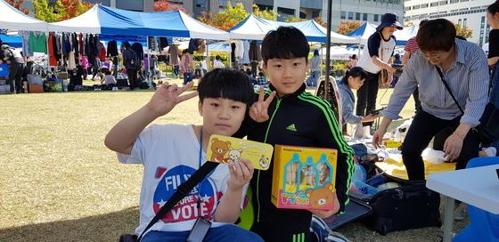 22일 대전시 서구 보라매공원에서 열린 위아자 나눔장터에서 윤채민(왼쪽), 김건우군이 판매할 물건을 들고 환하게 웃고 있다. 신진호 기자