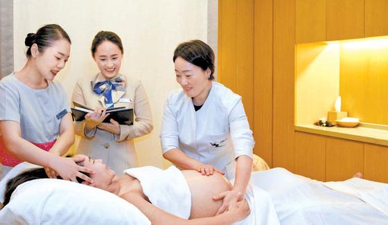 차움 테라스파 최희정 교수(오른쪽)와 이나리 전담 간호사(가운데)가 임신 28주차인 여성에게 전신 순환 마사지를 하고 있다. 프리랜서 조상희