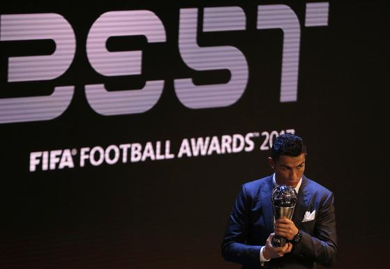 24일 영국 런던에서 열린 FIFA 올해의 선수상 시상식에서 남자 부문 최우수 선수로 선정된 크리스티아누 호날두가 트로피에 입맞추고 있다. [런던 AP=연합뉴스]