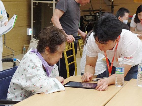 아리아케어 직원이 할머니에게 태블릿PC를 이용한 인지능력 개선 프로그램에 대해 설명하고 있다. [사진 아리아케어]