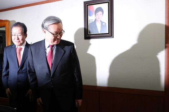 지난 3월 9일 당시 인명진 비상대책위원장(오른쪽) 당시 경남지사인 홍준표 지사를 접견하고 있다. 두 사람 뒤로 탄핵심판 선고를 하루 남긴 박근혜 대통령의 사진이 걸려있다. [중앙포토]