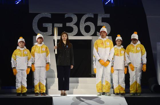 지난 2월 9일 강원도 강릉의 강릉하키센터에서 열린 평창동계올림픽 G-1기념행사에서 김연아(왼쪽에서 셋째), 크로스컨트리 국가대표 김마그너스(오른쪽 셋째) 등이 성화봉과 성화봉송 주자 유니폼을 공개하고 있다. [청와대사진기자단]