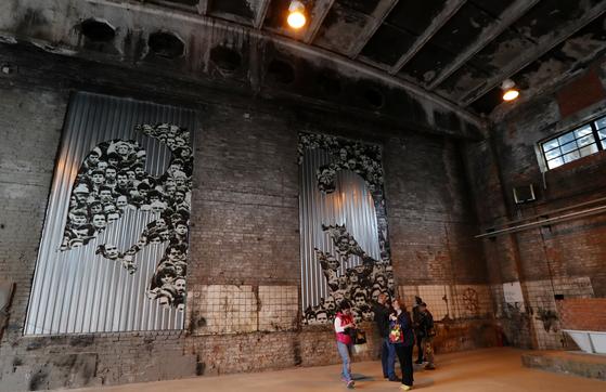 러시아 상트페테르부르크 외곽의 스트리트아트뮤지엄에서 열린 러시아혁명 100주녀녀 기념 전시회를 찾은 관람객들. 벽에는 '철의 장막'을 상징하는 철판에 소련 국민을 겹쳐 놓은 작품이 전시돼 있다. [조문규 기자]