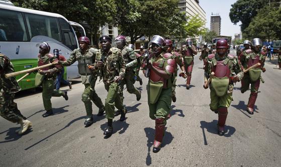 대통령 재선거를 앞둔 지난 16일(현지시간) 케냐 나이로비에서 벌어진 야권연합(NASA) 지지자들의 집회에서 경찰들이 몽둥이와 최루탄가스총을 들고 시위대를 향해 달려가고 있다. [AFP=연합뉴스]