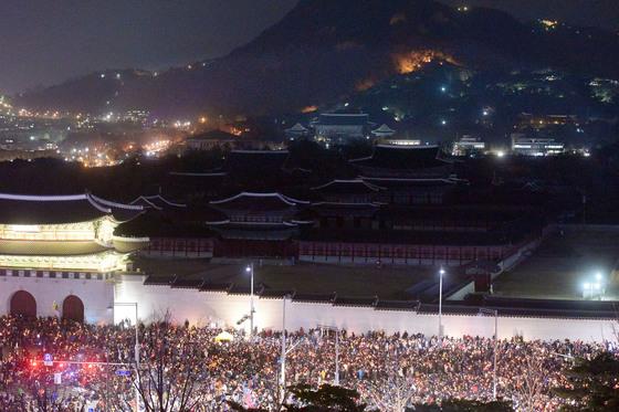 지난 12월 서울 광화문광장에서 박근혜 대통령 퇴진을 요구하는 6차 주말 촛불집회가 열린 가운데 촛불을 든 시민들 뒤로 청와대가 보이고 있다. [사진공동취재단]