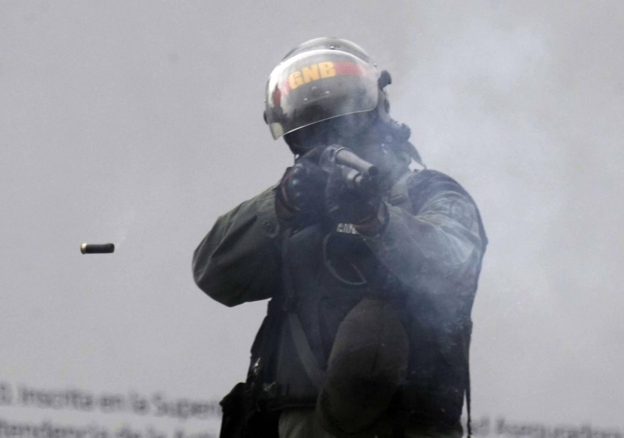 베네수엘라 경찰이 지난 6월 7일(현지시간) 카라카스에서 반정부 시위대를 향해 총(shotgun)을 쏘고 있다.[AP=연합뉴스]