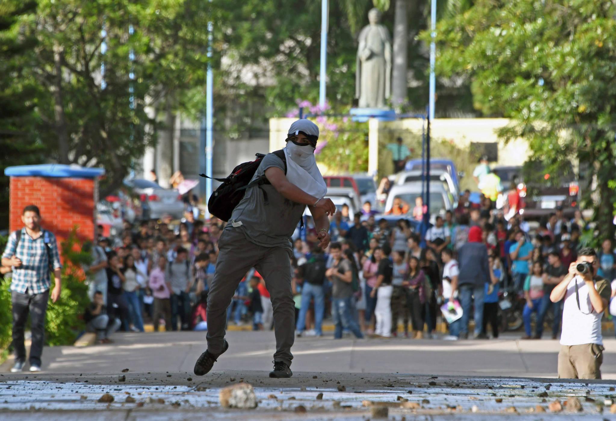 온두라스 대학생들이 지난 18일(현지시간) 수도 테구시칼파에서 반정부 시위를 벌이며 경찰을 향해 돌을 던지고 있다.[AFP=연합뉴스]