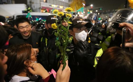 촛불집회에 참가한 중고교생들이 청와대 인근 내자동에서 바리케이드를 치고 막아선 경찰에게 꽃을 건네고 있다. 학생들은 '비폭력', '밀지마' 등을 외치며 평화 분위기를 만들었다. [중앙포토]