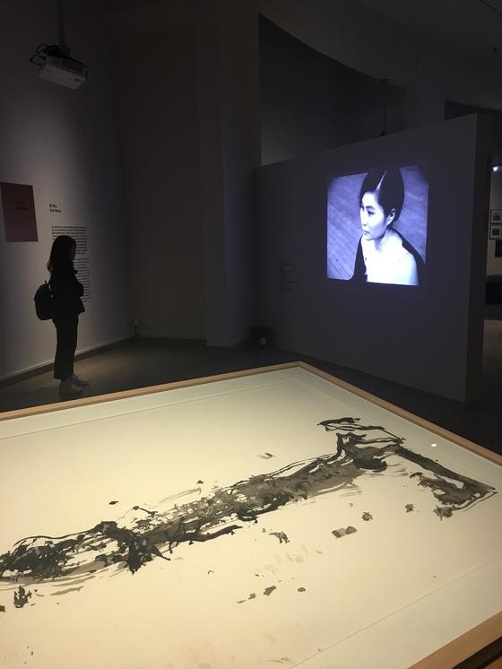 앞은 백남준이 '머리를 위한 선' 퍼포먼스에서 그린 평면작품 중 하나. 뒤 영상은 오노 요코의 '컷 피스'. [이후남 기자]
