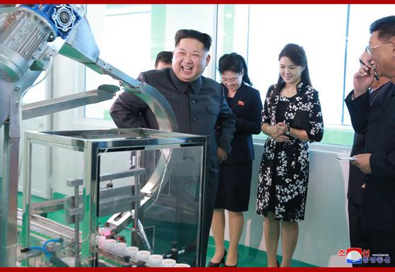김정은 북한 노동당위원장이 평양화장품 공장을 현지지도했다고 북한 관영 언론들이 29일 보도했다. 부인 이설주(오른쪽 둘째)도 동행했다.[사진=조선중앙통신]