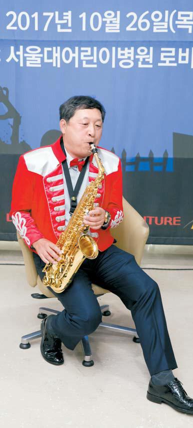 롯데월드는 1995년 7월 20일부터 서울대어린이병원을 찾아 위문공연을 해왔다. 사진은 지난 26일 있었던 100회 기념 공연에서 색소폰으로 동요를 연주하는 박동기 대표. [사진 롯데월드]