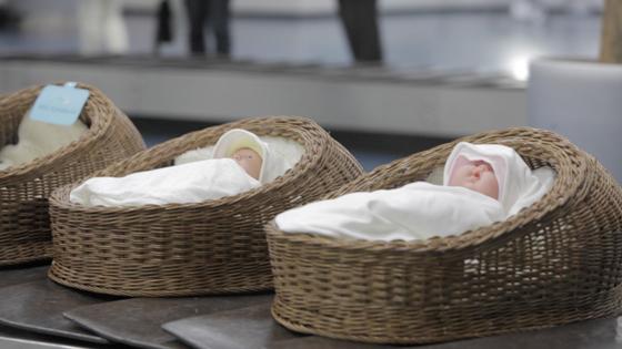 수화물 벨트에 실린 아기 바구니를 통해 해외로 입양되는 아기들의 불편한 현실을 전달한 동영상의 한 장면. [사진=HS애드]