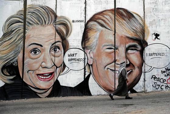 이스라엘 분리의 벽에 묘사된 2016년 미국 대선 후보 힐러리 클린턴과 도널드 트럼프 미국 대통령 그래피티 앞을 지나가는 팔레스타인 행인. [AFP=연합뉴스]