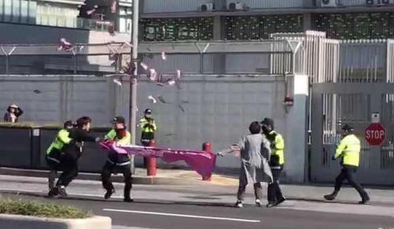 지난달 17일 낮 서울 종로구 주한미국대사관 앞에서 반미성향 청년단체 '청년레지스탕스' 회원 2명이 미국 비판 시위를 벌이다가 경찰에 붙잡히고 있다. [연합뉴스]