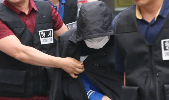 지난 6월 충북 충주에서 인터넷 기사를 살해한 혐의로 구속 기소된 권모(55)씨가 현장검증을 위해 범행 현장으로 가고 있다. [연합뉴스]