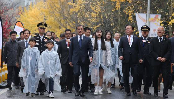 문재인 대통령이 3일 오전 충남 천안시 중앙소방학교에서 열린 제55주년 소방의날 기념식에 참석하기 위해 충혼탑을 참배한 뒤 순직 소방관 유족들과 함께 입장하고 있다.[연합뉴스]