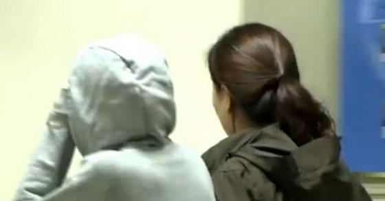 지난 1일 오후 경기 용인 세가족 살해 사건 피의자의 아내 정모(32 ·사진 왼쪽)씨가 경찰조사 후 유치장으로 이동하고 있다. [연합뉴스]