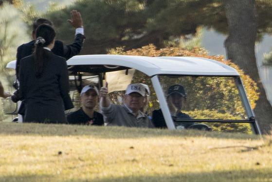도널드 트럼프 미국 대통령과 아베 신조 일본총리, 마쓰야마 히데키 프로골프 선수가 5일 일본 가스미가세키 컨트리클럽 공프장에서 함께 카트를 타고 이동하던 중, 트럼프 대통령이 엄지손을 치켜올리고 있다. [AP=연합뉴스]