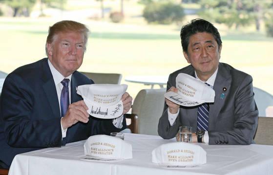 도널드 트럼프 미국 대통령(왼쪽)과 아베 신조 일본 총리가 5일 사이타마 현 가스미가세키CC에서 오찬을 하기에 앞서 함께 서명한 모자를 들어 보이고 있다. [연합뉴스]