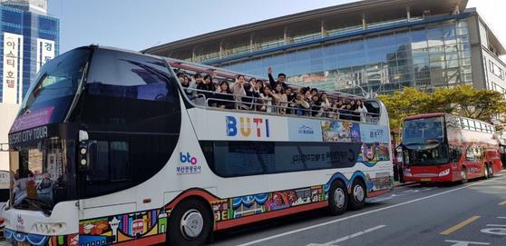 부산시티투어버스를 탄 탑승객들이 밖을 바라보며 손을 흔들고 있다. [사진 부산관광공사]