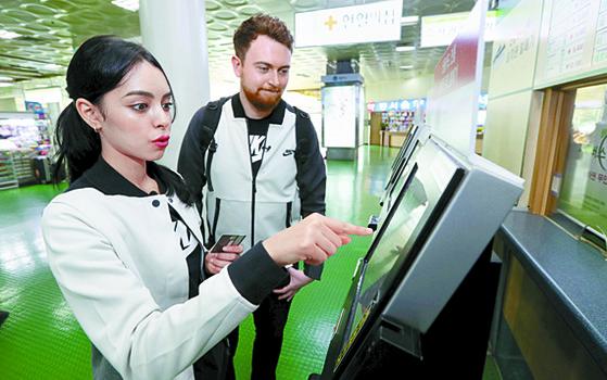 우메이마와 니콜라이가 동서울터미널에서 횡계행 버스표를 예매하고 있다. 승차권 판매 기계를 통해 손쉽게 발권했다. [강정현 기자]