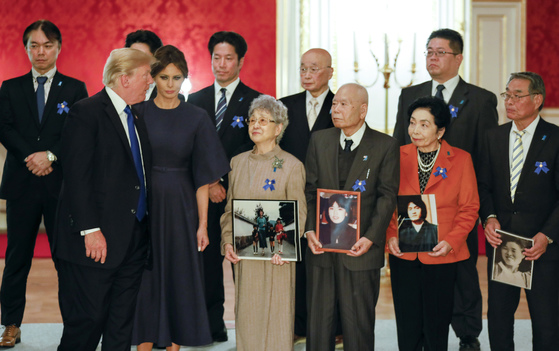 U.S. President Donald Trump and first lady Melania speak to families of Japanese abducted by North Korea in Tokyo Monday, Nov. 6, 2017. Fourth from right is Sakie Yokota and third from right is Akihiro Arimura. (Kimimasa Mayama/Pool Photo via AP)
