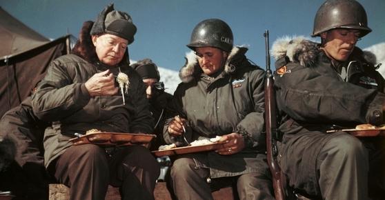 1952년 12월 한국전쟁 도중 드와이트 아이젠하워 대통령이 당선인 신분으로 서부전선 최전방 미군 부대를 방문해 장병들과 야외에서 함께 식사하고 있다.