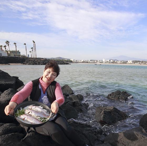표선어촌식당 송금산(45) 사장이 제주 바다를 배경으로 옥돔국 재료들을 들어보이고 있다. [중앙포토]