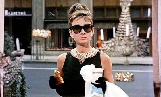 영화 '티파니에서 아침을' 한 장면. 주인공(오드리 헵번)은 자신이 사온 빵과 커피를 들고 티파니 본점 쇼윈도 밖에서 열망과 좌절이 섞인 표정으로 아침을 먹고 있다. [영화 스틸]