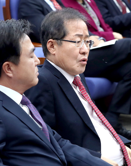 홍준표 자유한국당 대표(오른쪽)와 김태흠 의원이 13일 국회에서 열린 의원총회에 앞서 이야기하고 있다. 홍 대표는 이날 정부·여당의 적폐청산 활동에 맞서 보수진영 전체가 단합할 것을 주문했다. [박종근 기자]