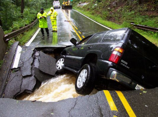 SUV 차량 한 대가 2011년 허리케인 '아이린'이 몰고 온 폭우에 유실된 미국 뉴저지 키넬론의 도로에 28일(현지시각) 처박혀 있다. 키넬론 경찰은 복구 작업이 몇 달은 걸릴 것이라고 밝혔다.[AP=연합뉴스]