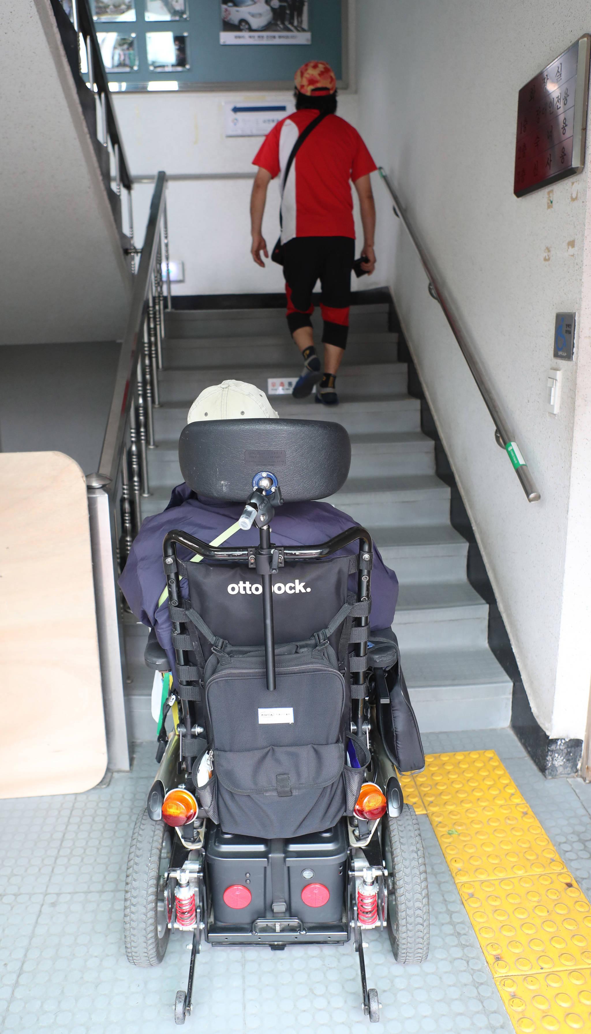 전동휠체어를 탄 채 계단을 바라보고 있는 지체장애인. 앞으로 중증장애인이 읍면동 주민센터를 직접 방문하지 않고도 온라인으로 장애인연금을 신청할 수 있게 된다. [중앙포토]