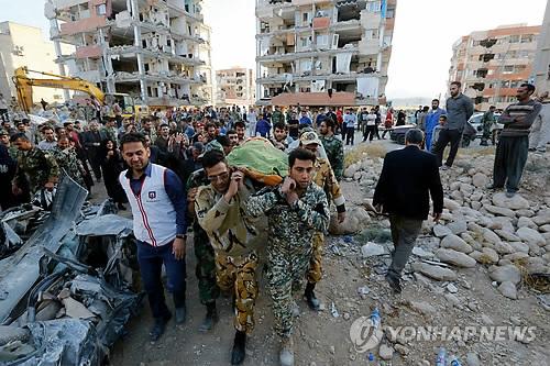 13일 이란 북서부 케르만샤주(州) 폴 자하브의 지진 현장에서 군인들이 희생자 시신을 옮기는 모습. [연합뉴스]