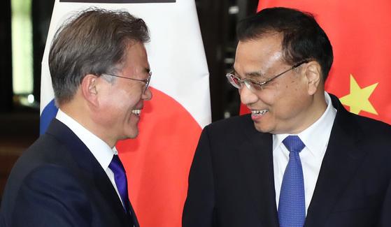 문재인 대통령이 13일 오후 '제31차 ASEAN 정상회의'가 열리는 필리핀 마닐라 소피텔 호텔에서 리커창 중국 총리와 회담장 앞에서 만나고 있다. 청와대 사진기자단