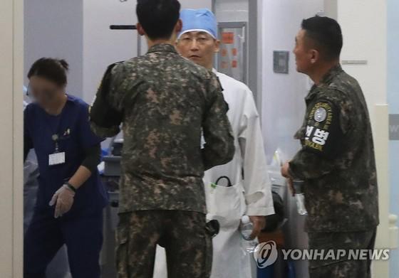 아주대병원에서 이국종 교수와 군 관계자가 총상을 입은 귀순 북한군의 상태에 대해 얘기를 나누고 있다. [사진 연합뉴스]