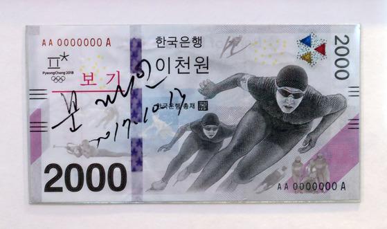 한국은행은 평창 동계올림픽에서 처음으로 2000원 기념은행권 발행했다. 왼쪽에 문재인 대통령의 친필서명이 보인다.앞면에는 스피드스케이팅 선수들의 모습이 등장한다. 최승식 기자