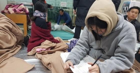 15일 오후 포항시에서 발생한 규모 5.4의 지진으로 수능 시험이 일주일 미뤄진 가운데 체육관에 대피한 고3 수험생이 공부하고 있는 모습이 포착됐다. [사진 연합뉴스]
