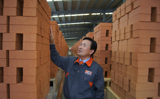 한삼화 회장이 포장을 앞둔 황토벽돌을 점검하고 있다. [사진 삼한C1 제공]
