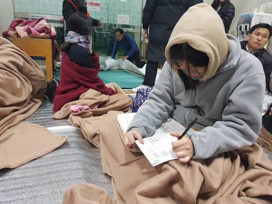 15일 경북 포항에서 규모 5.4 지진이 발생한 뒤 주민들이 대피한 북구 흥해실내체육관에서 한 고3 학생이 수능시험 공부를 하고있다. [연합뉴스]